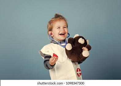 Kids playing with toys. Happy child veterinarian smile with teddy bear on blue background. Veterinary clinic game. Future profession concept. Boy in doctor uniform examine toy pet with stethoscope