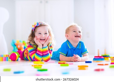 Kids playing with toys. Two children, cute toddler girl and funny baby boy, playing with wooden toy blocks, building towers at home or day care. Educational child toys for preschool and kindergarten.