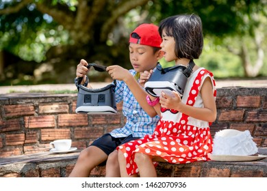 Kids playing and watching virtaul reality glasses gadgets, Asian family children on travel in summer time, white coffee cup set and white hat on ground, boy wearing red cap, blurred green big tree