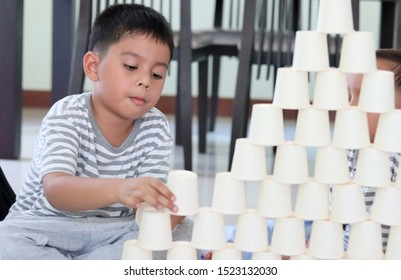 Kids Playing with white paper cups building a cup tower on floor.