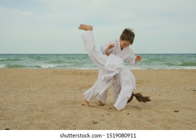 Kids practicing Aikido on the beach. Healthy lifestyle and sports concept