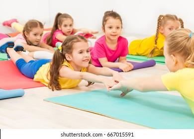 Kids practicing gymnastics with female teacher