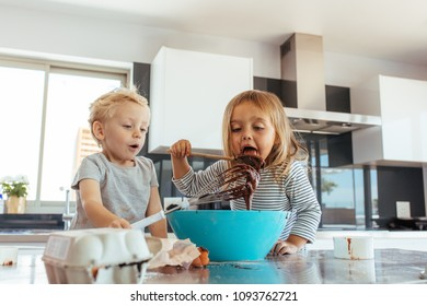 Kids preparing chocolate cake batter with girl licking batter from spatula with her brother holding a whisk. Small kids preparing cake batter in kitchen.