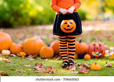 Kids with pumpkin on Halloween. Little girl in witch costume and hat playing in autumn park. Child at Halloween trick or treat. Kid trick or treating. Toddler with lantern. Children with candy bucket.