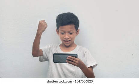 Kids punched to the air celebrating his winning playing online games on mobile phone