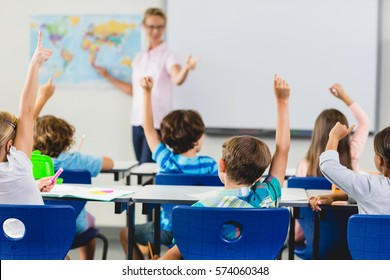 Kids raising hand in classroom at school