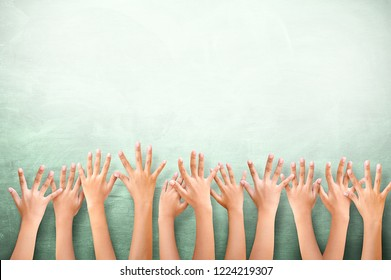 kids Raising hands up together showing on green Chalkboard.