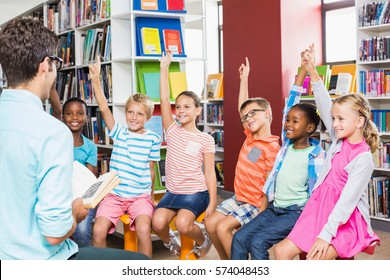 Kids raising their hands in library at school
