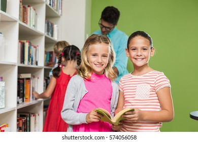 Kids reading book in library at school