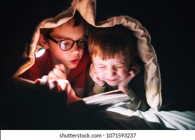 kids reading a book under the blanket. the elder brother reads a scary tale aloud. Little boy in fright closed his eyes and covered his ears