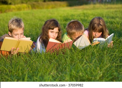 Kids are reading books on the green grass