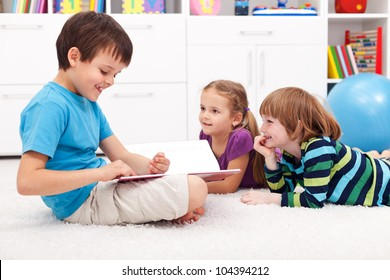 Kids reading funny story at home - smiling happily