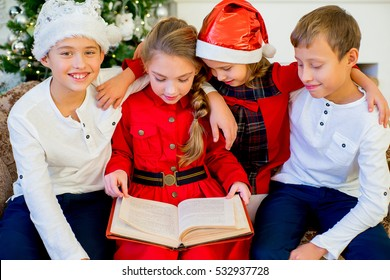 Kids reading a story book together under a Christmas tree on Christmas time at home