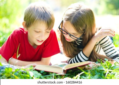 Kids reading together enjoying a book laying on the grass outdoors