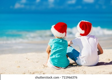 Kids in red Santa hats having fun at tropical beach during Christmas vacation playing together with sand
