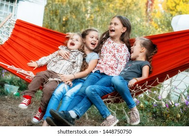 Kids relax in hammock. Children playing and laughing merrily, swinging in an orange hammock