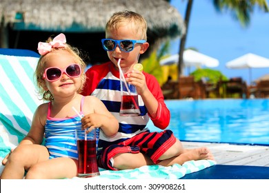 kids relax on tropical beach resort and drink juices, family vacation