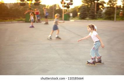 Kids ride on roller skates on skate yard