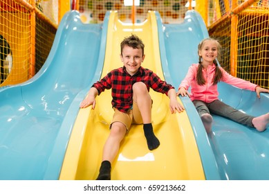 Kids riding from childrens slides in game center