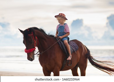 Kids riding horse on beach. Children ride horses. Cute blond kid in cowboy hat with USA flag on summer vacation on California or Florida coast. American boy on his pony on a ranch. Child and animal.