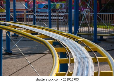 Kids roller coaster yellow rails in amusement park in the afternoon.
