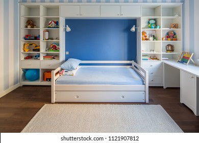 Kid's room in a modern style with striped blue-white walls and a parquet with a carpet on the floor. There is a white bed with pillows, lockers and shelves with toys and books, table. Horizontal.