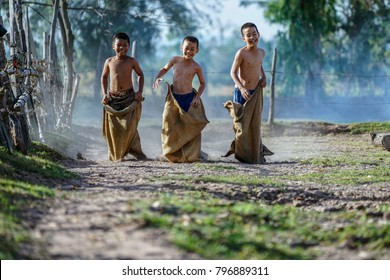 Kids run in the sack,Children playing Old thailand traditional sports,rural country,Thailand,