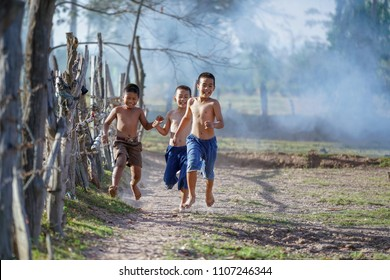 kids runing in rural thailand,Children playing in rice field countryside of asia.