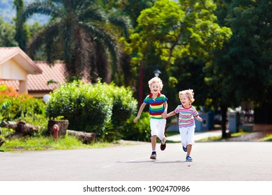Kids running. Children run on city suburbs street on sunny summer day. Little boy playing outdoor. Friends and brothers play. Healthy activity for school child. Active kid exercise.
