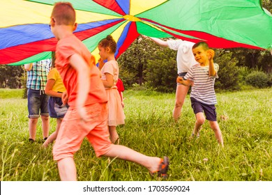 Kids running in circle under colorful parachute