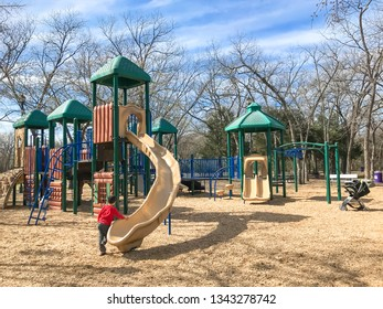Kids running at colorful playground during wintertime in Lewisville, Texas, USA.