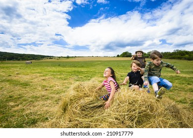 Kids running and jumping in a pile of straw, summer day