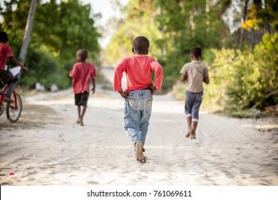 Kids running on beach sand. Children running to play in Stone Town, Zanzibar Island, Tanzania.