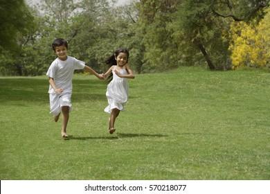 kids running in park, holding hands