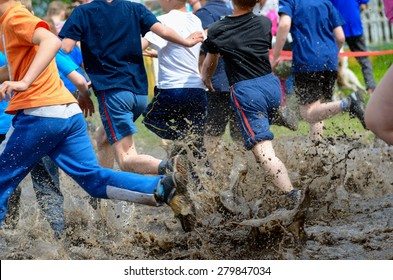Kids running trail race, legs in mud and water