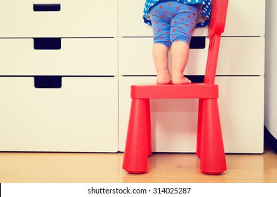kids safety concept- little girl  climbing on baby chair