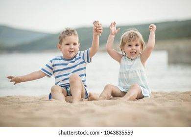Kids at sandy beach, eating ice cream and hands up