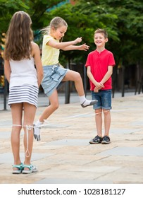 Kids in school age playing together with chinese jumping rope outdoors. Focus on boy