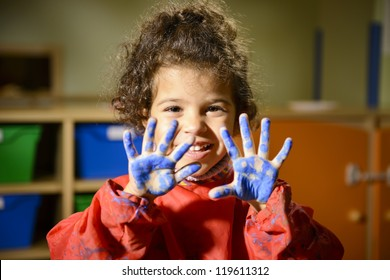 Kids, school and education, happy female child having fun and painting in kindergarten, showing hands to camera