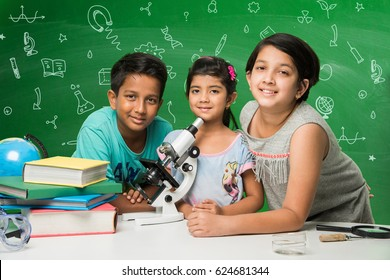 Kids and science concept - cute indian little kid student/scientist studying science or experimenting with microscope and Chemicals with diagrams/doodles drawn over green chalkboard in the background