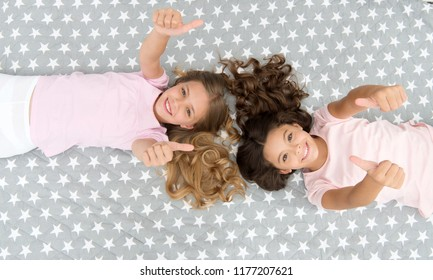 Kids show thumbs up gesture. Girls children on bed top view. Pajamas party concept. Girls just want to have fun. Girlish secrets honest and sincere. Friends have nice time pleasant leisure.