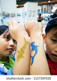 Kids showing their tattoos on hand.