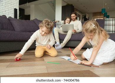 Kids siblings playing on floor while parents using laptop at home, preschool boy holding toy car, little girl drawing with colored pencils in album, family spending time together in living room