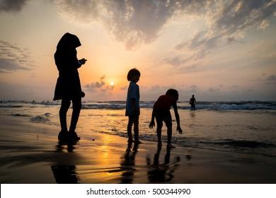 Kids silhouettes having happy time on sea beach near sunset