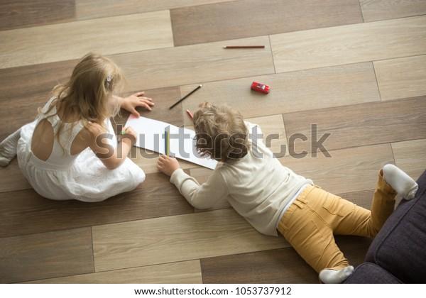 Kinderschwester und Bruder, die zusammen auf hölzernem, warmem Boden im Wohnzimmer spielen, kreative Kinder Junge und Mädchen, die sich zu Hause amüsieren, Geschwisterfreundlichkeit, Fußbodenheizung, Draufsicht
