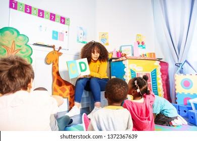 Kids sit around teacher and learn alphabet