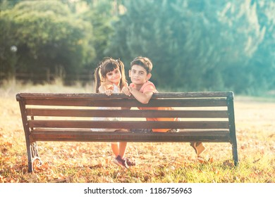 Kids sitting on a bench in autumn park. Innocent childhood concept