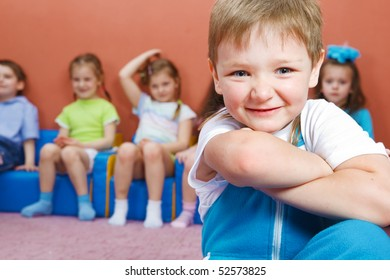 Kids sitting on chairs, preschool boy in front of them