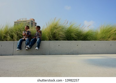 Kids Sitting on a Ledge to the Left.