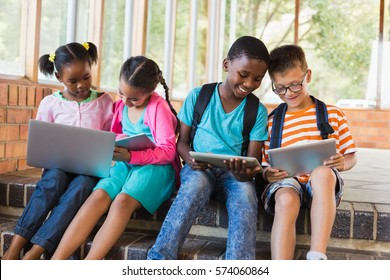 Kids sitting on staircase using laptop and digital tablet at school